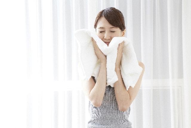 タオルを顔に当てる女性
