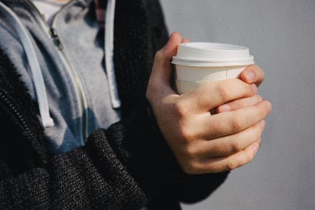 コーヒーを持つ人